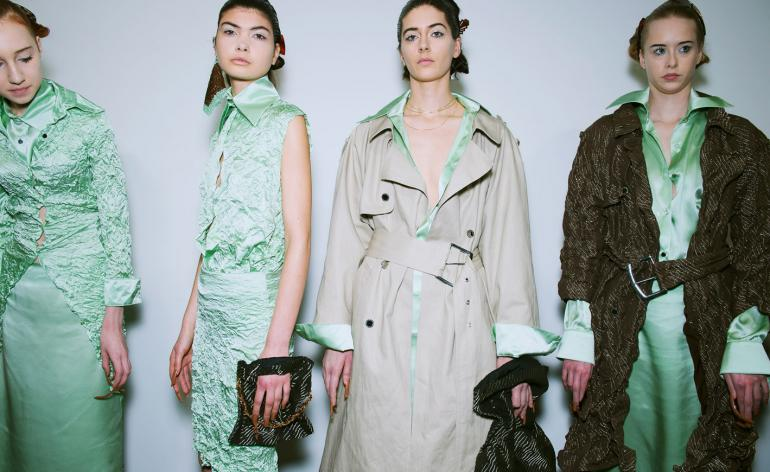 Models wear mint green silk dresses and shirts, layered with slouchy outerwear
