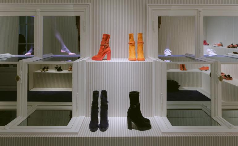Shoes are lined up on shelves, behind sees walls of windows with model's legs peeping through