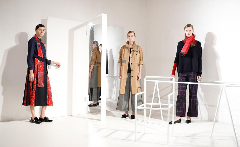 Models wear a range of trenchcoats, checkered wide-leg trousers and statement scarfs