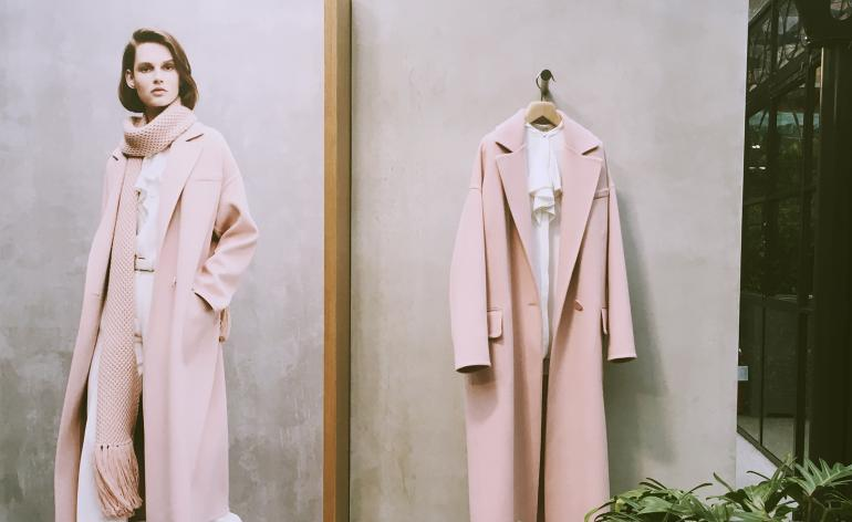Model wears a sugar pink coat with a matching scarf, another sugar pink coat hangs to the right