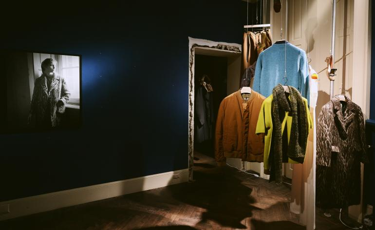 Outerwear is hung from the ceiling of a dilapadated room, art hangs on the walls
