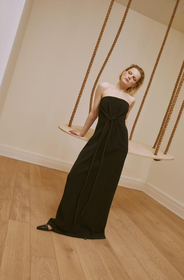 Model can be seen wearing an exaggerated black evening dress, tied with a thick cord at the waist