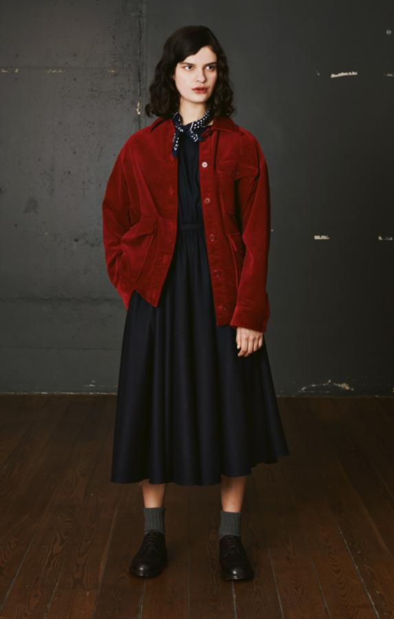 Aspesi: model wears a red corduroy jacket with pleated navy skirt