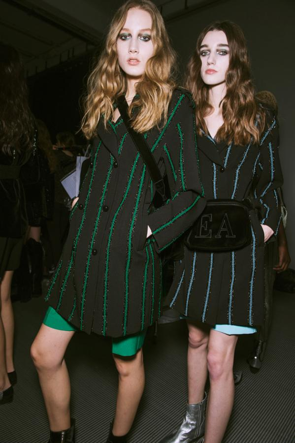 Models wear green and black pinstripe suits with shorts