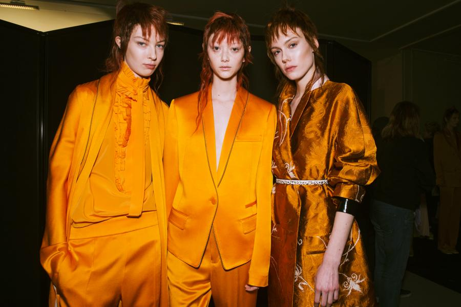 Models are seen wearing bright orange suits, dresses and gowns