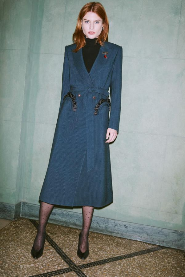 Model wears a navy tailored wool coat with belt