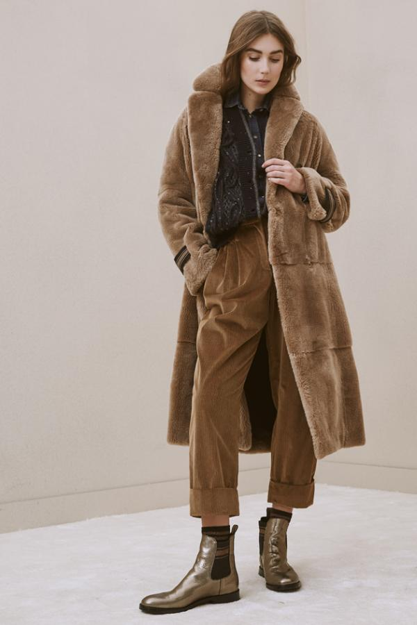Model wears a long fur coat with corduroy trousers and chelsea boots