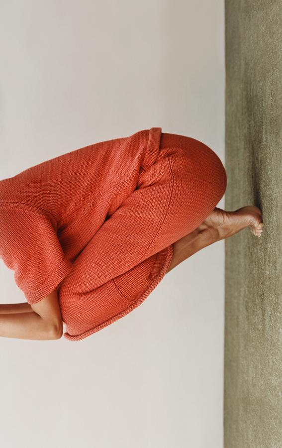 COS Magazine yoga pose in orange knitwear