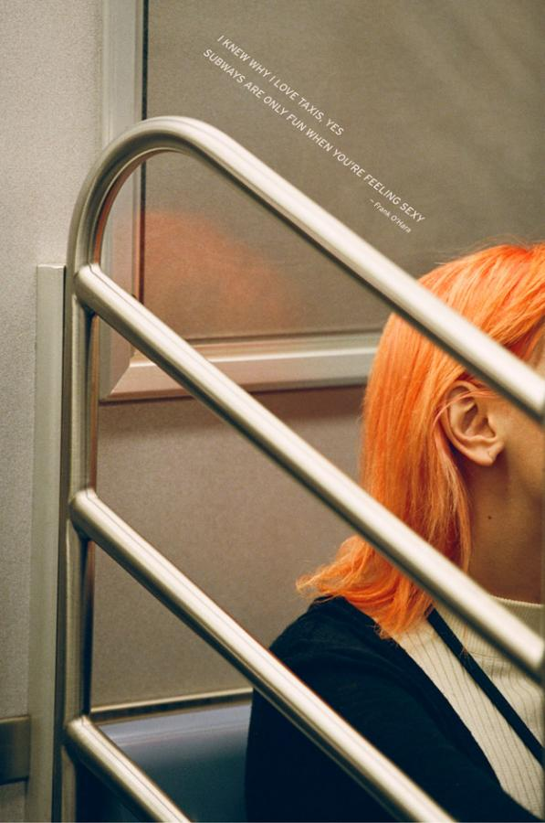 A young woman with orange hair on the New York subway
