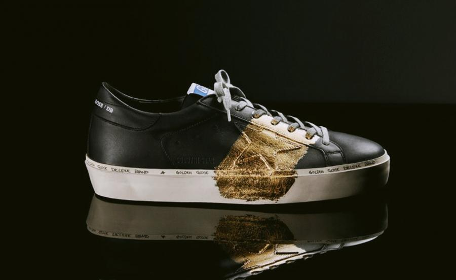 Image of black sneakers with a white sole, with a golden detail over the side and upper