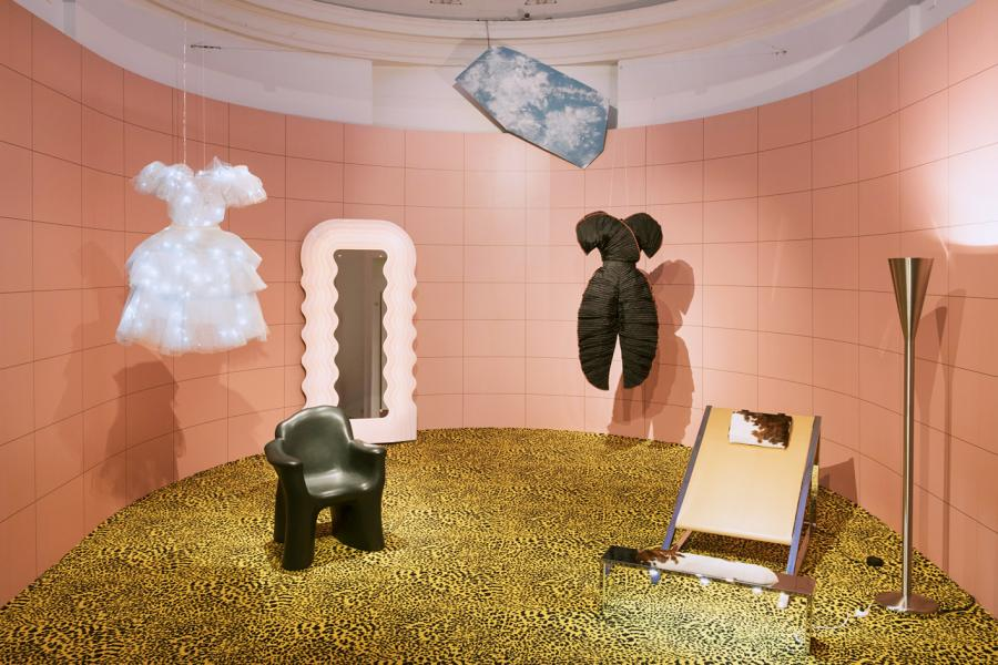 Exhibition view sees dresses suspended from the ceiling, surrounded by pink tiles