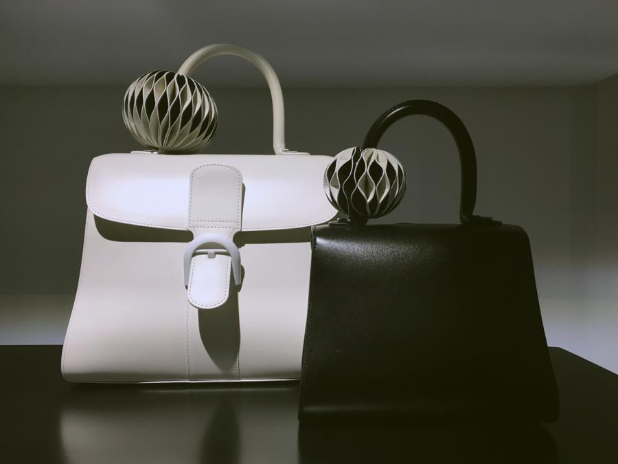 White and black leather bags are seen sit-in upon a shelf, each has a leather origami accessory