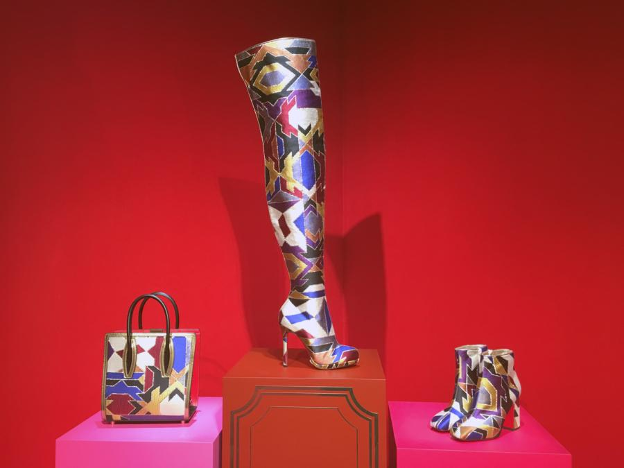 A thigh-high heeled boot, covered in a futuristic tapestry sits on a red plinth