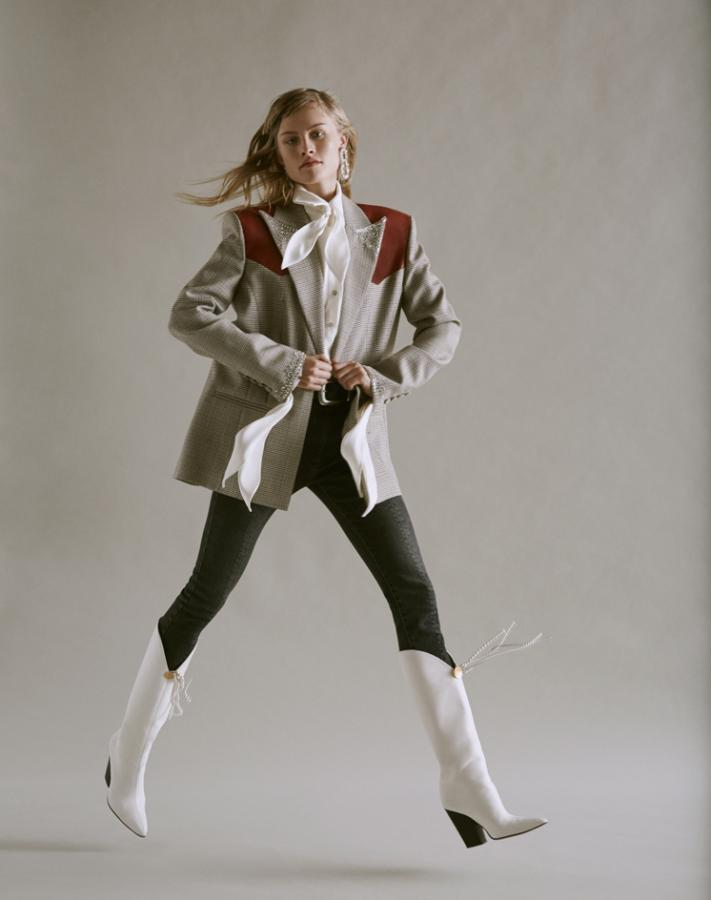 Model wears a check tailored blazer with white cowboy boots and a bow sleeve shirt