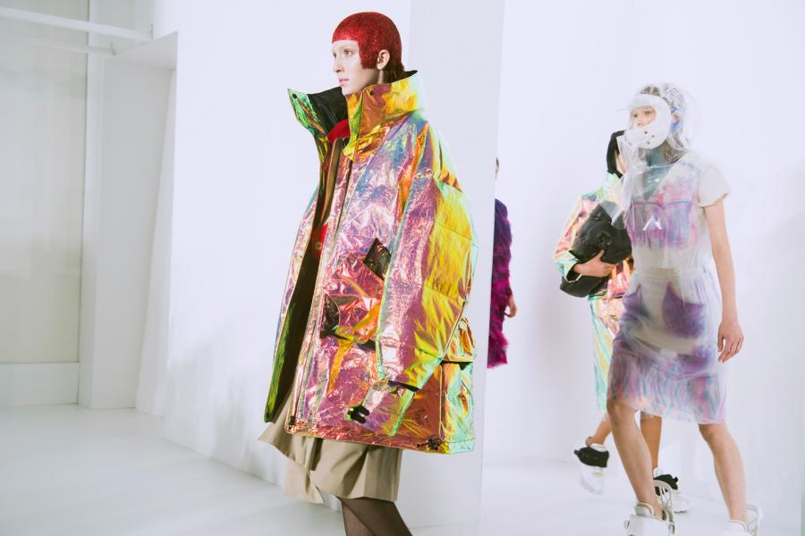 Model wears a oversized, bright holographic puffer coat. Another wears a transparent plastic dress with sneakers