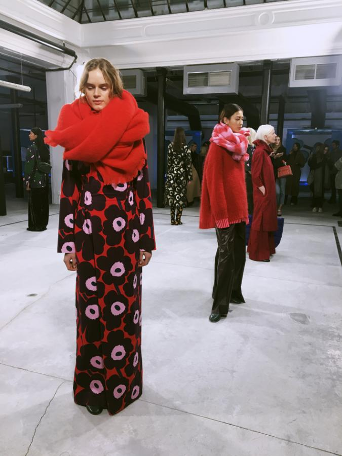 Models are seen wearing print pattern skirts with oversized, red outerwear, including coats and scarfs