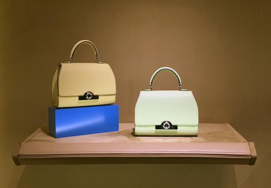 Pastel coloured bags in blue, orange and green sit upon a wooden shelf