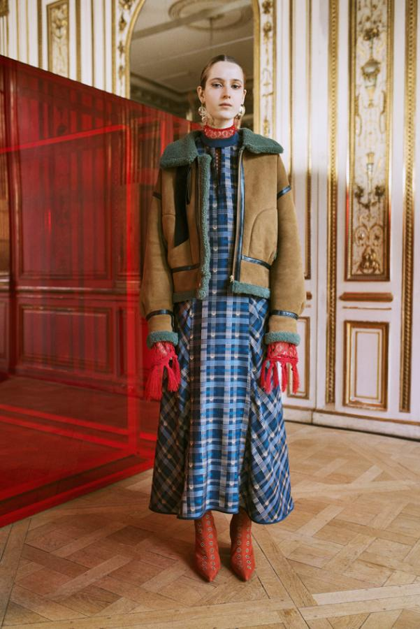 Mame Kurogouchi: Model wears a blue checkered dress with a shearling jacket