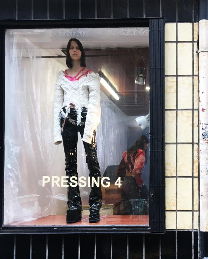 Model stands in a shop window wearing black jeans and a white distressed jumper