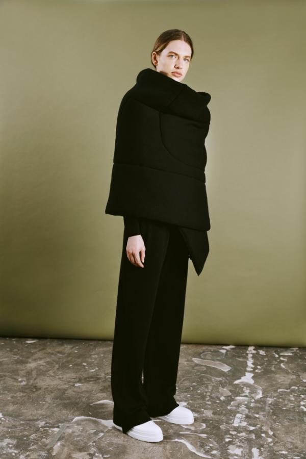 Model wears black tailored trousers and a black puffer coat, that wraps around the body.