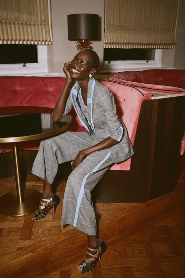 Model sits in a velvet bar wearing an oversized checkered suit, with a sporty blue stripe running up both the trouser and blazer