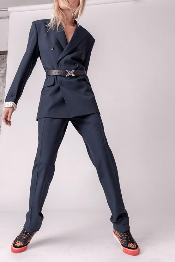 Female model wears a navy trouser suit cinched with a belt and trainers
