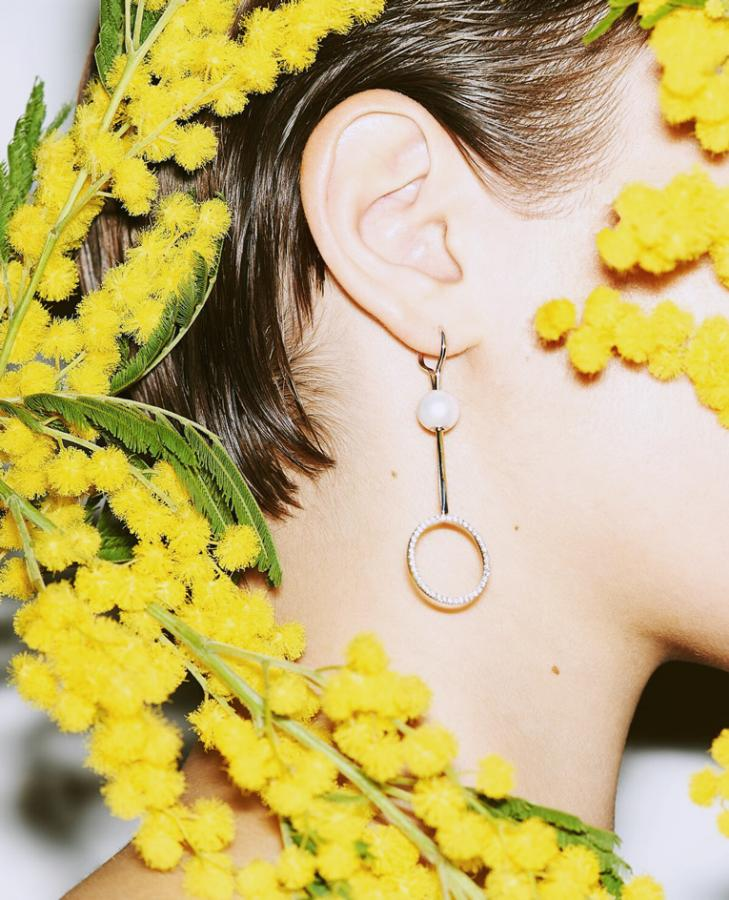 Delfina Delettrez: Model wears a circular earring surrounded by flowers