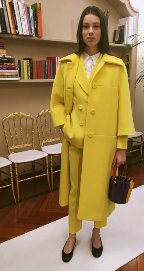 Model wears a bright yellow trench coat, with matching trousers and blazer