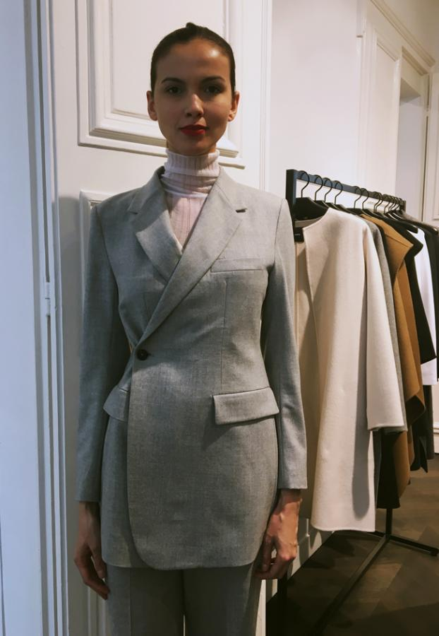 Model wears a light grey double-breasted jacket with a pink high neck top
