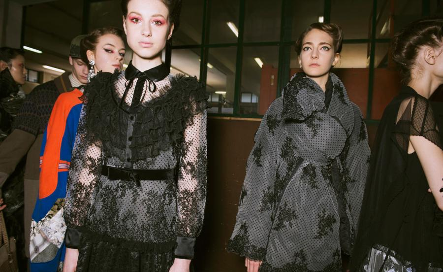 Models wear black mesh dresses, embellished with frills and floral patterns