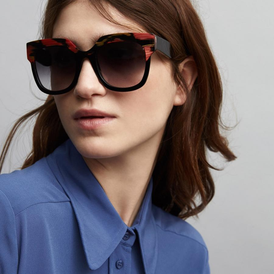 Model wearing black wide frame sunglasses