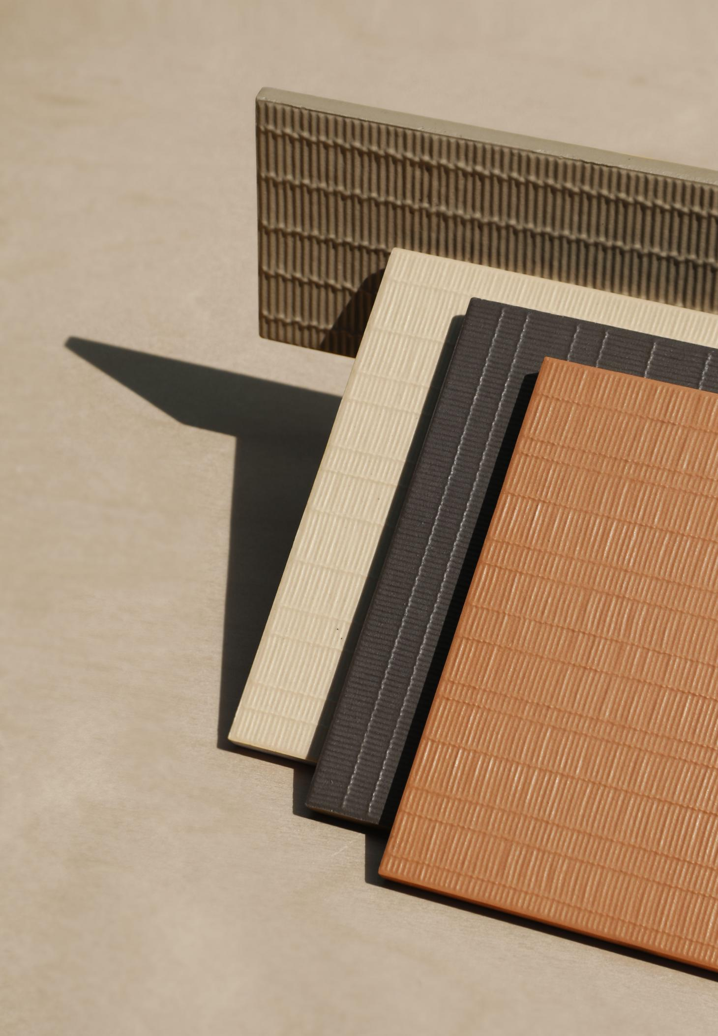 Tiles with textured surfaces in beige, brown and olive green
