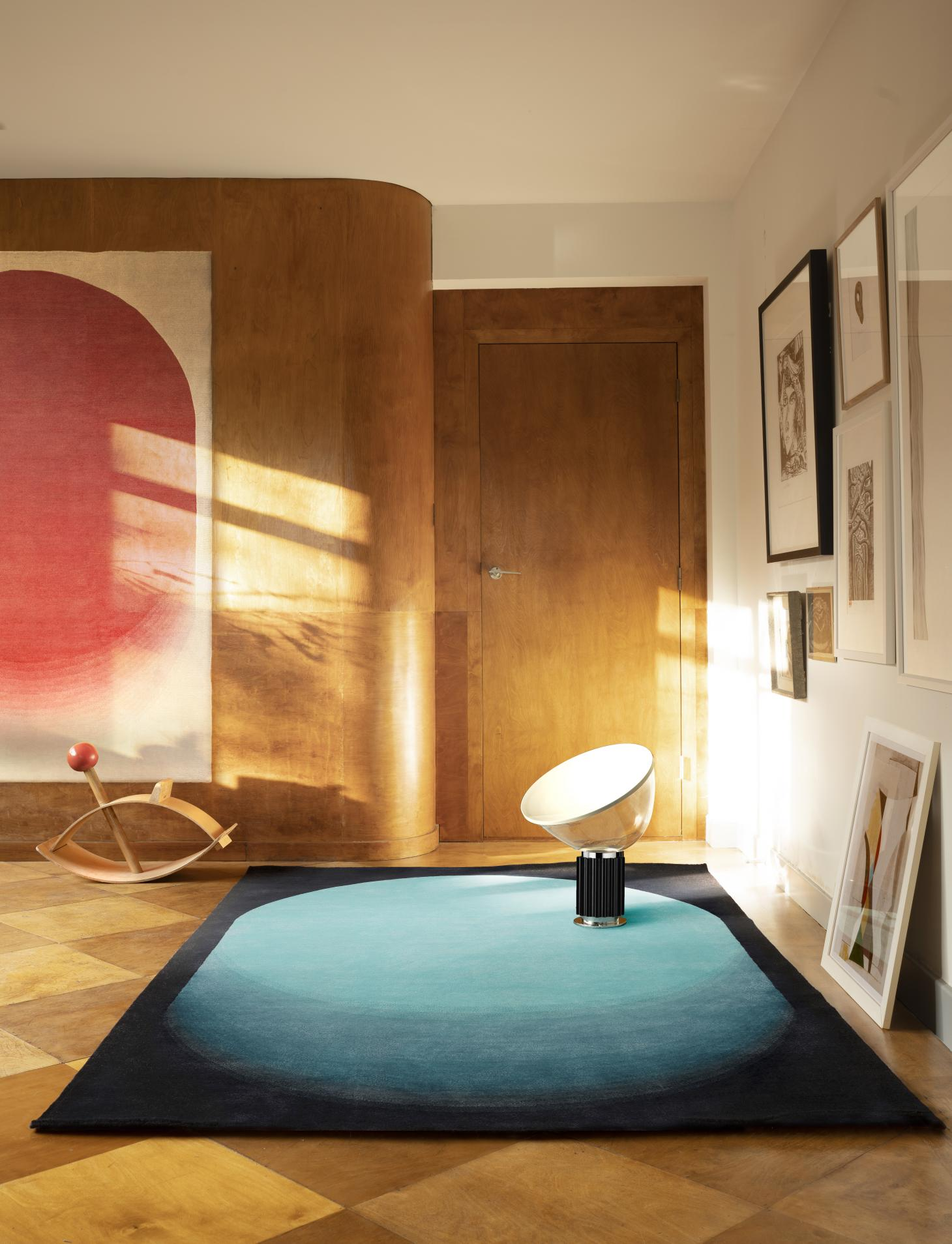 A rug with a blue oval on black background placed on the parquet floor of a room featuring wooden walls with a further rug in white and red hanging vertically