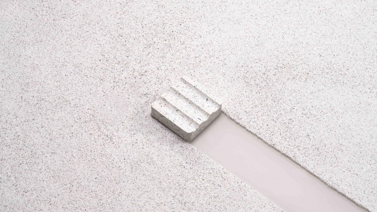 Terrazzo pen rest made of recycled materials on a surface of white and gray ebonite offcuts