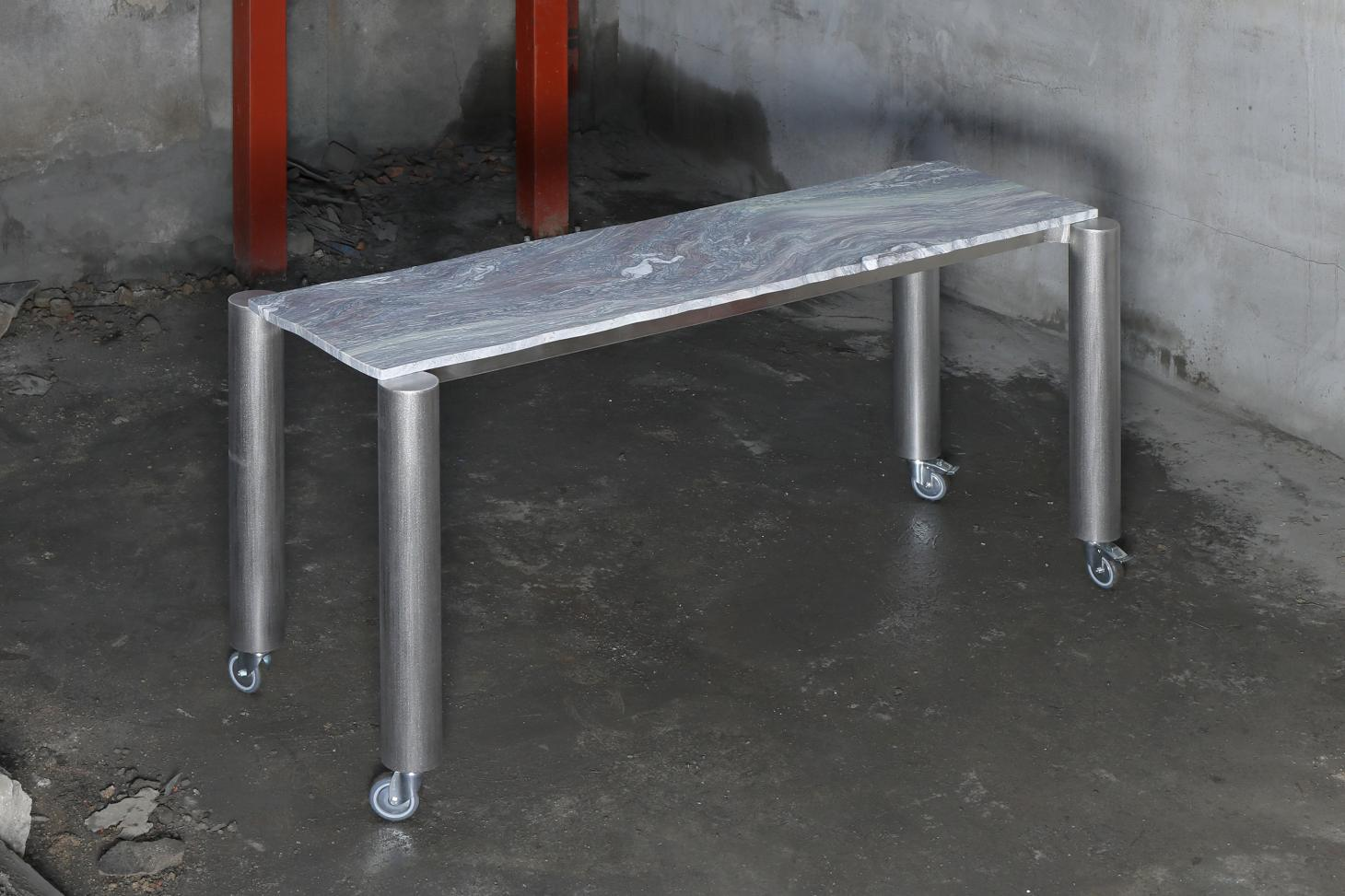 Narrow work table with wheels, featuring metal legs and marble top