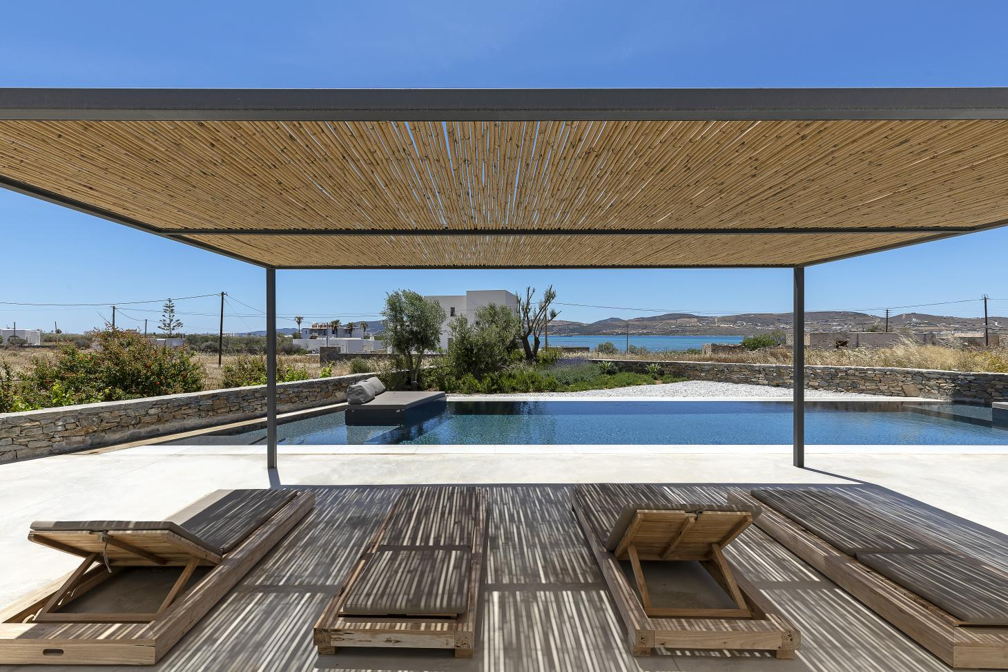 swimming pool and deck chairs under blue skies in KITE House in Greece