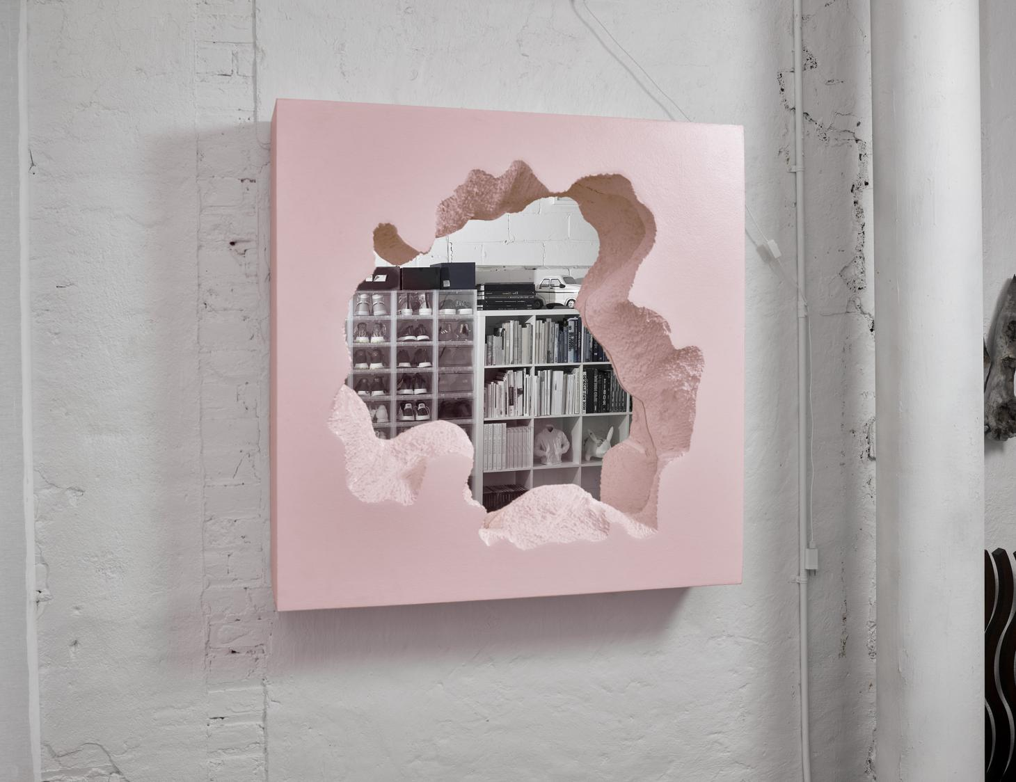 Pink framed mirror reflecting shelves with shoes and books in the Snarkitecture New York studio
