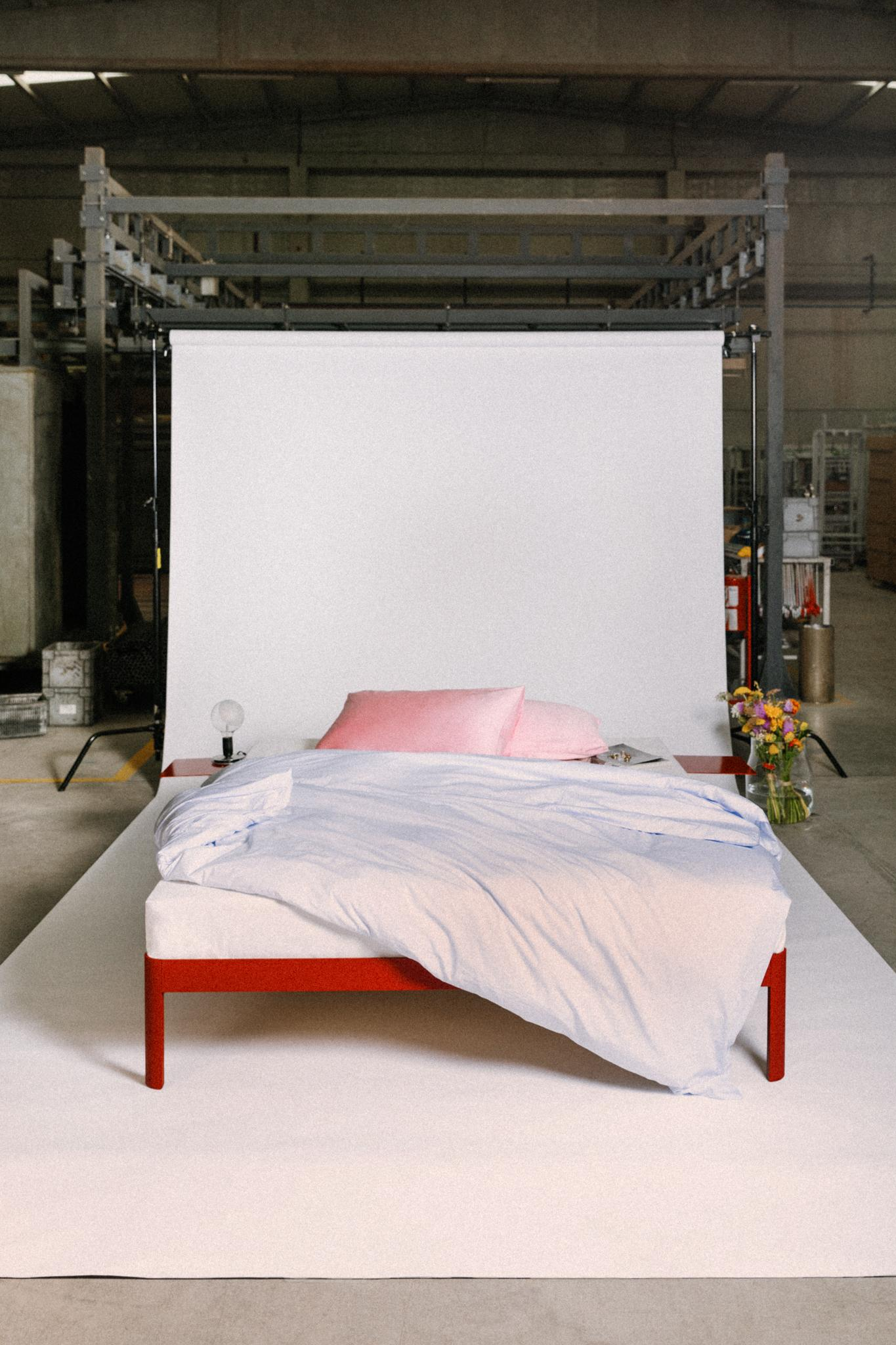 The ReFramed bed with red frame and side tables, with white bedding and pink pillows, photographed on a set in the factory. The edges of a white paper background are visible, and on the bed sides are a small lamp and a vase with flowers