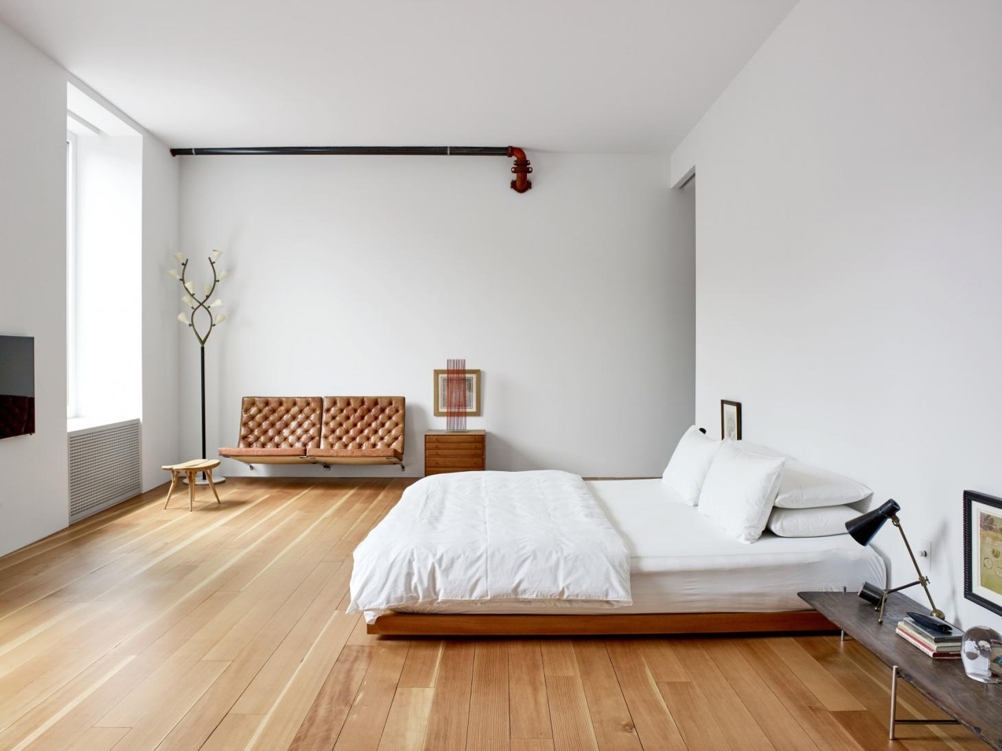 Michael Maharam bedroom in his New York Apartment, minimally decorated with a platform bed with white bedlinen