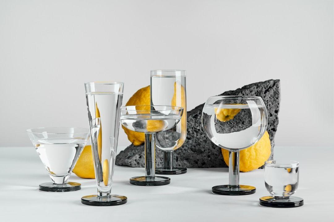 Drinking glasses by Tom Dixon, with rocks and lemons in the background. Included are clear glasses for water, champagne, wine and cocktails, they all feature a black glass base
