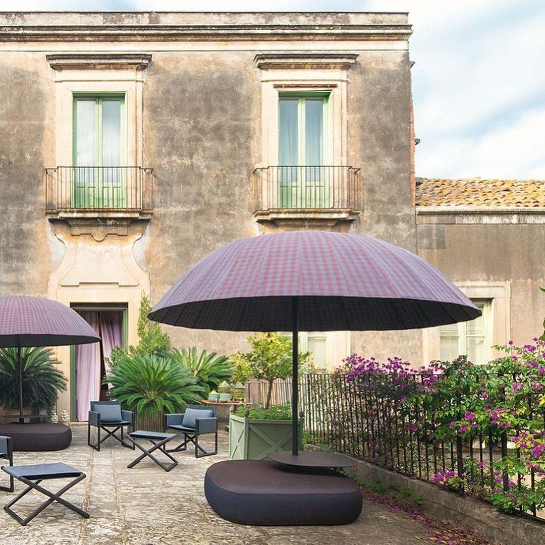 Shot against the backdrop of a historical villa is Paola Lenti's Bistro Parasol, with a checkered purple shade and inflated seat as a base. In the garden of the villa is other outdoor furniture and purple flowers