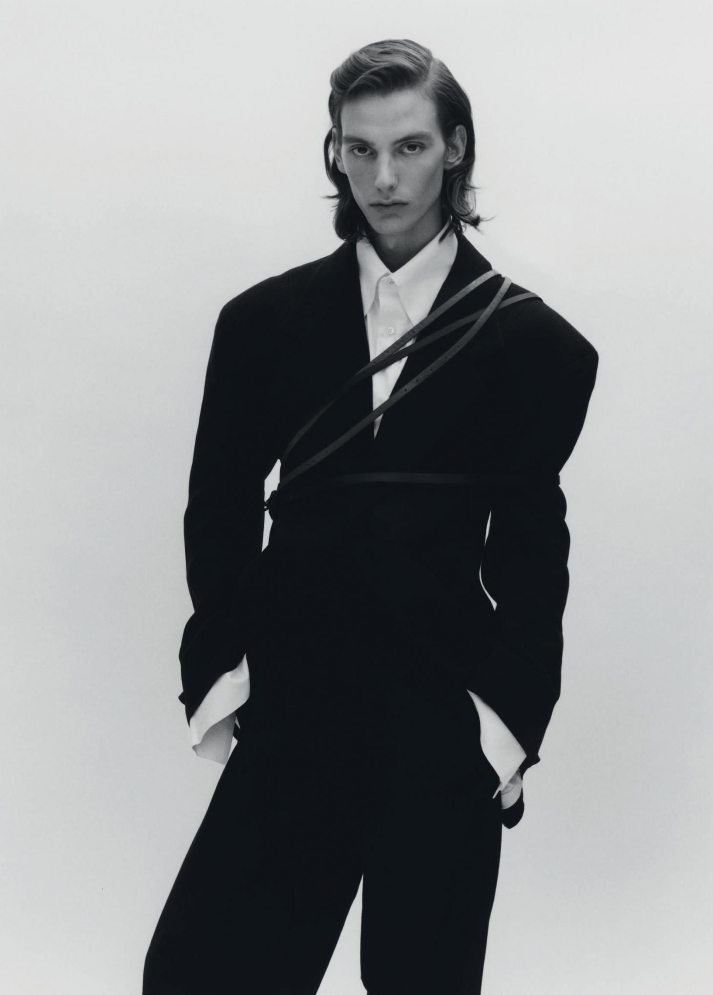 Man stands in a black smoking jacket with a white shirt
