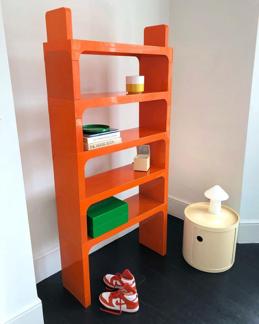 Red plastic shelving unit by Kartell, on a black wooden floor
