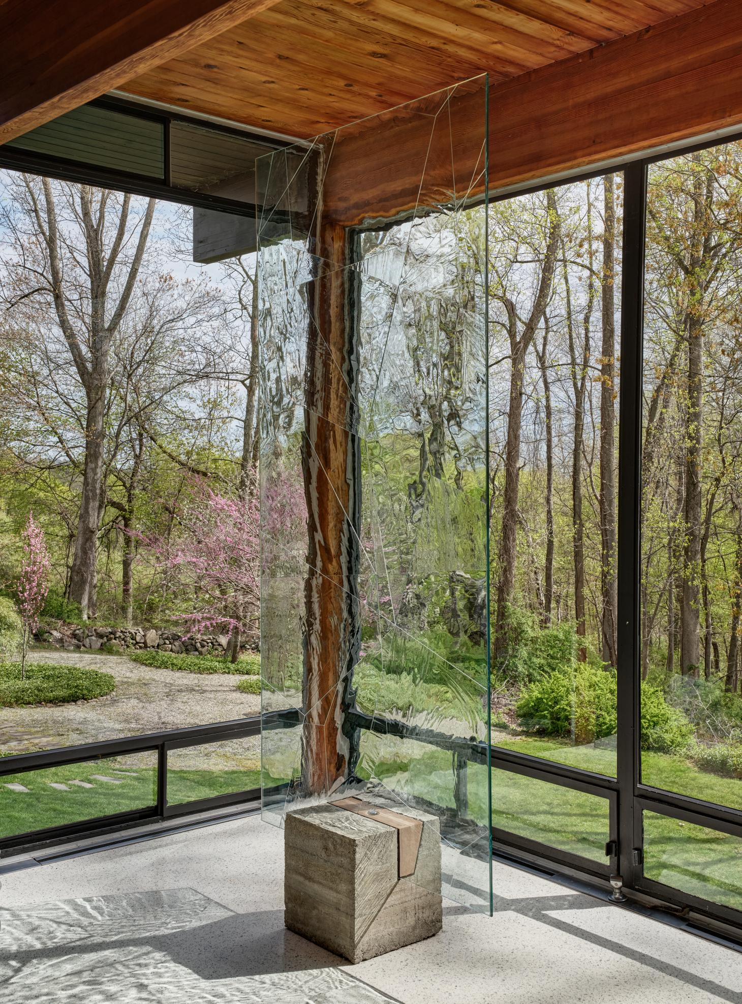 Interior shot of house by Gerald Luss with glass and steel details and terrazzo floor furnished with metal table