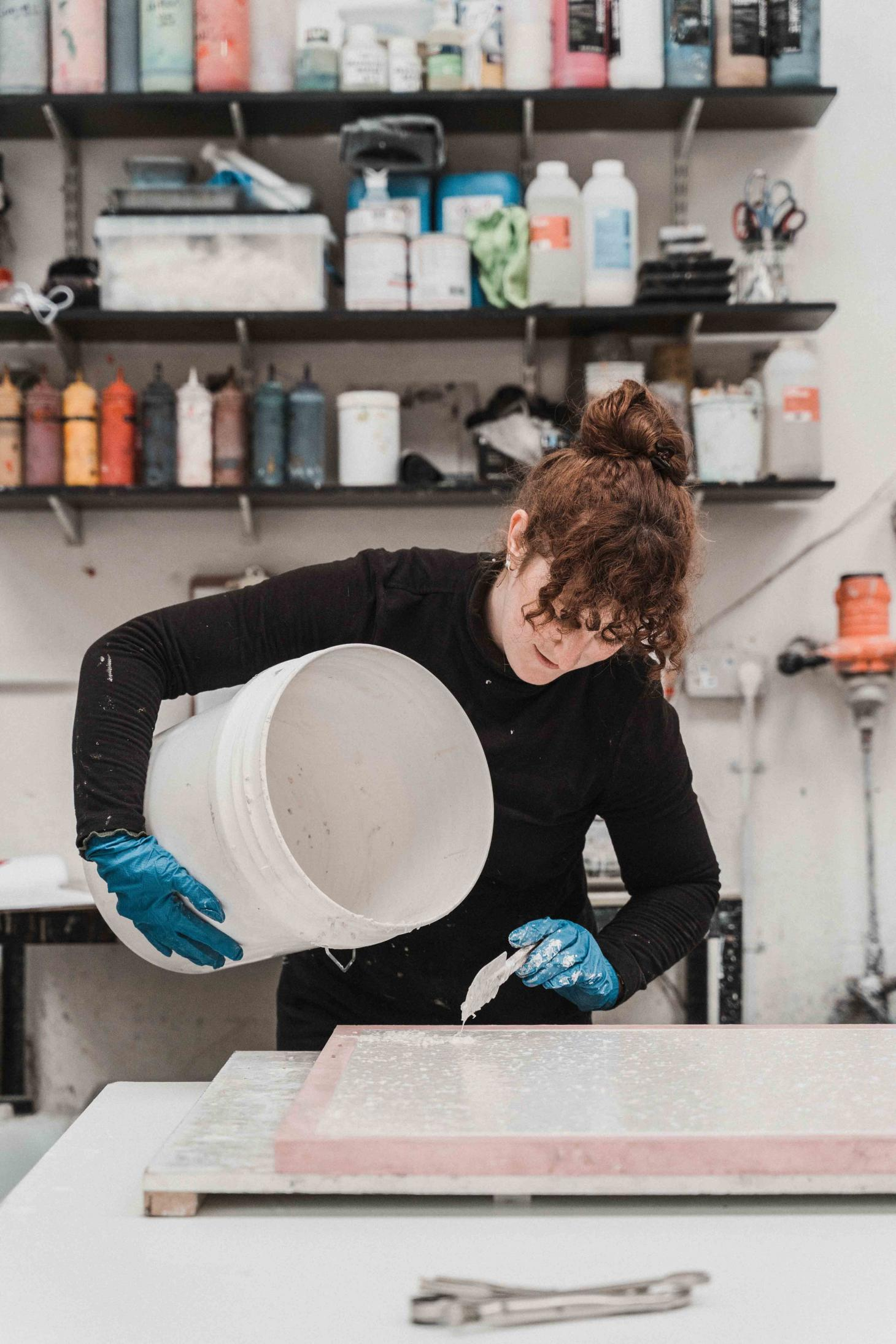Olivia Aspinall creating terrazzo surface in her Nottingham studio with samples on shelves in the background