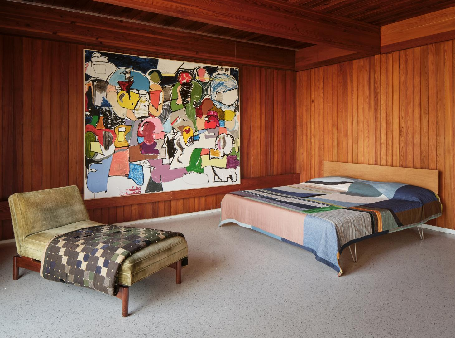 Wood panelled bedroom with terrazzo floor, colourful textiles on bed and day bed and art on the wall