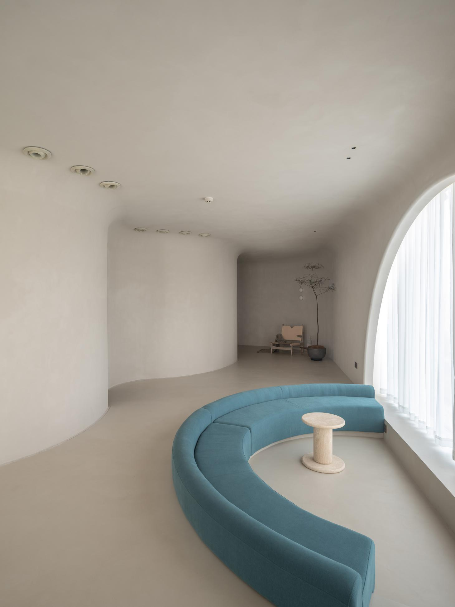 Lounge area of Soul Realm Spa House in Hangzhou, China with white curving walls