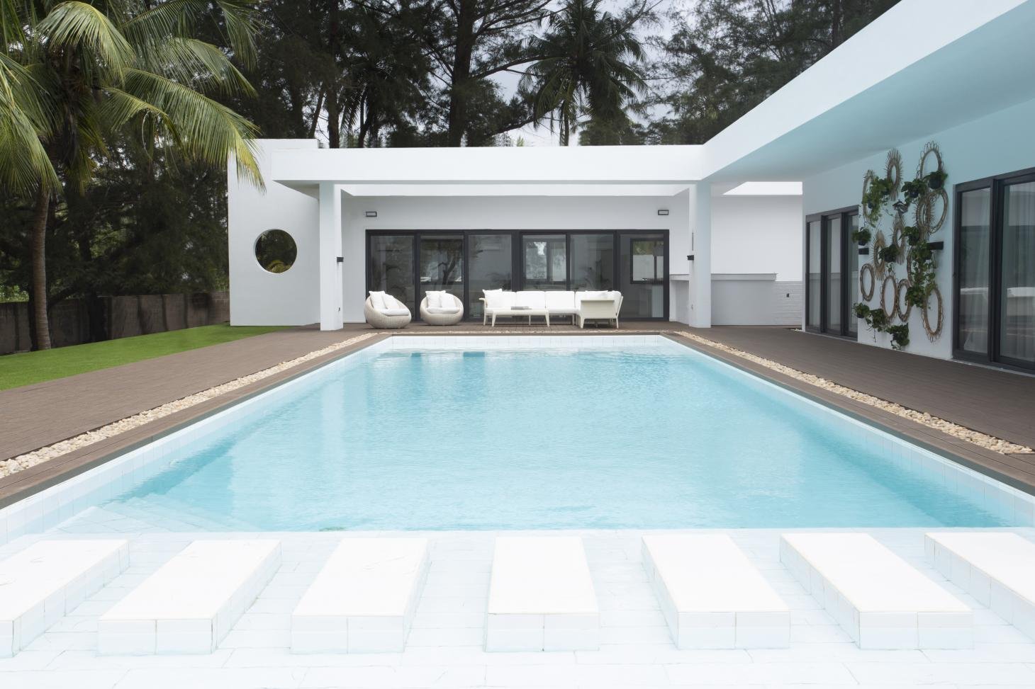 looking at low modernist Nigerian villa over swimming pool