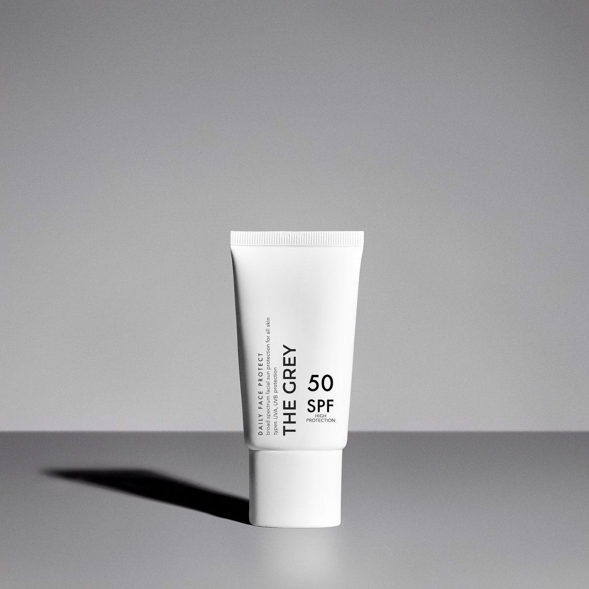 The Grey Daily Face Protect sunscreen in white bottle against grey background