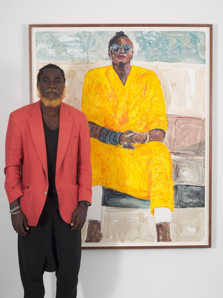 Serge Attukwei Clottey stands in front of one of his works in the exhibition 'Beyond Skin' at Simchowitz Gallery, Los Angeles